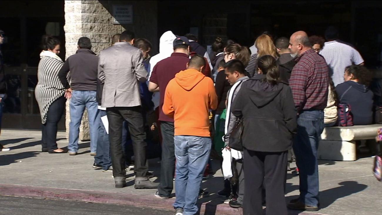 This file photo shows people forming a line outside a California Department of Motor Vehicles office.