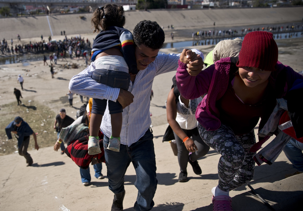 <div class='meta'><div class='origin-logo' data-origin='AP'></div><span class='caption-text' data-credit='AP Photo/Ramon Espinosa'>Migrants walk up a riverbank at the Mexico-U.S. border after getting past a line of Mexican police at the Chaparral border crossing in Tijuana, Mexico, Sunday, Nov. 25, 2018.</span></div>