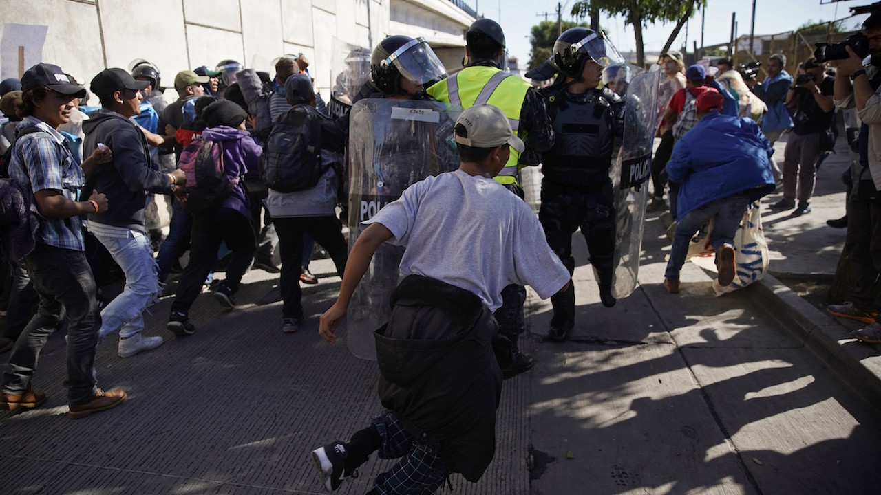 <div class='meta'><div class='origin-logo' data-origin='AP'></div><span class='caption-text' data-credit='AP Photo/Ramon Espinosa'>Migrants break past a line of police as they run toward the Chaparral border crossing in Tijuana, Mexico, Sunday, Nov. 25, 2018, near the San Ysidro entry point.</span></div>