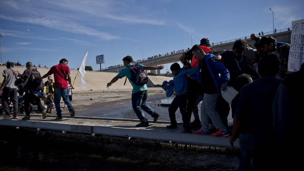<div class='meta'><div class='origin-logo' data-origin='AP'></div><span class='caption-text' data-credit='AP Photo/Ramon Espinosa'>Migrants cross the river at the Mexico-U.S. border after getting past a line of Mexican police at the Chaparral crossing in Tijuana, Mexico, Sunday, Nov. 25, 2018.</span></div>