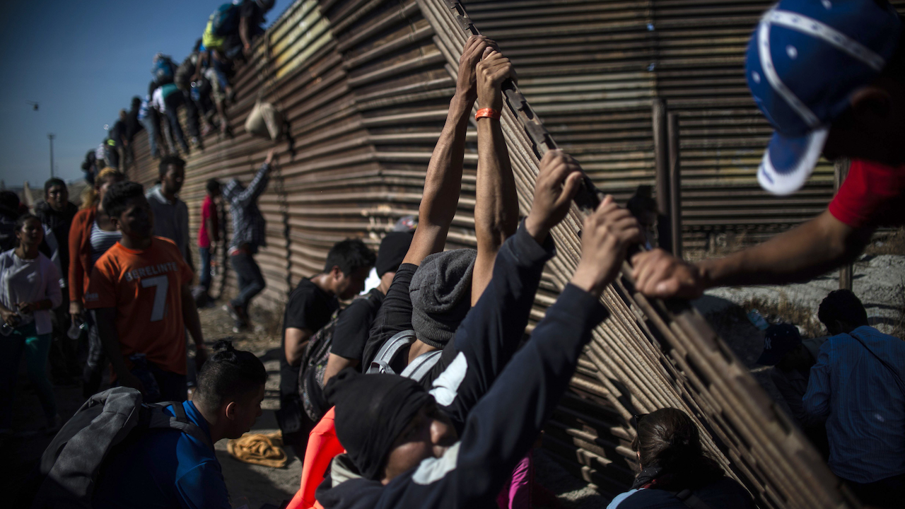 <div class='meta'><div class='origin-logo' data-origin='Creative Content'></div><span class='caption-text' data-credit='Pedro Pardo/AFP/Getty Images'>A group of Central American migrants climbs the border fence between Mexico and the United States as others try to bring it down in Tijuana, Mexico, on November 25, 2018.</span></div>