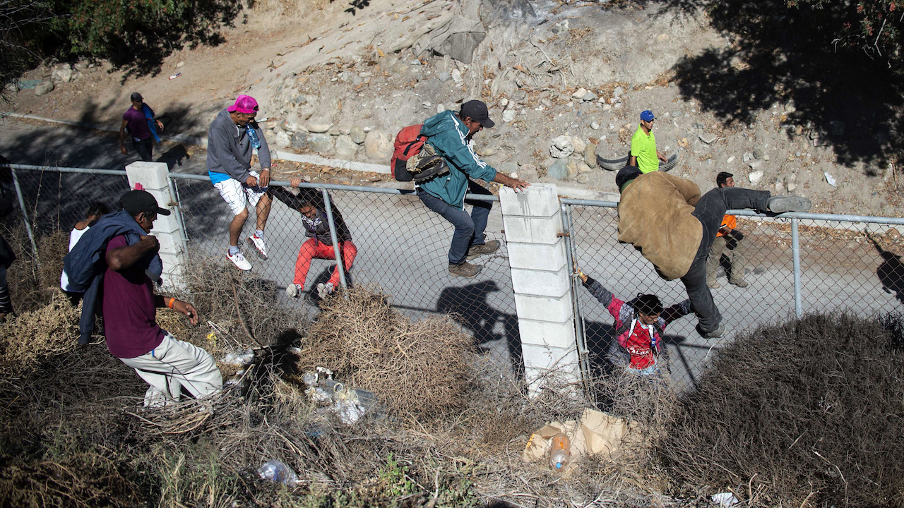 <div class='meta'><div class='origin-logo' data-origin='Creative Content'></div><span class='caption-text' data-credit='Pedro Pardo/AFP/Getty Images'>A group of Central American migrants crosses over a fence as they try to reach the border fence between Mexico and the United States, in Tijuana, November 25, 2018.</span></div>