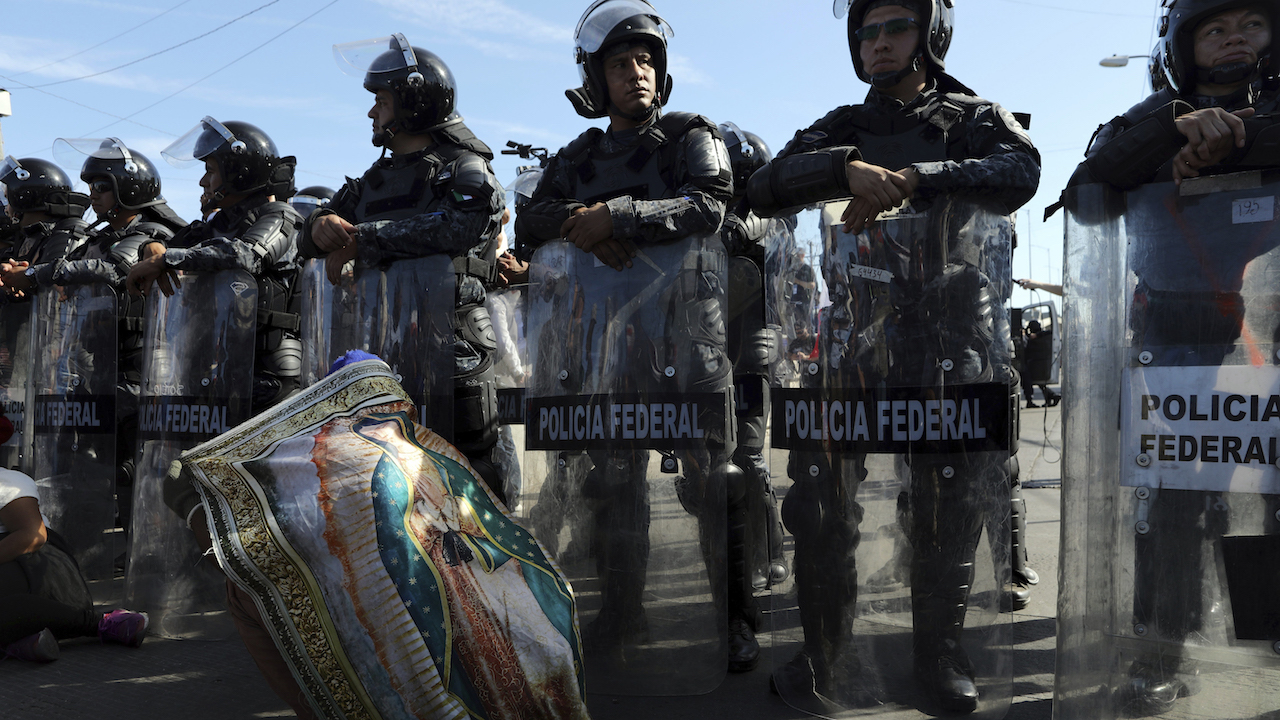 <div class='meta'><div class='origin-logo' data-origin='AP'></div><span class='caption-text' data-credit='AP Photo/Rodrigo Abd'>Mexican federal police stand guard over a migrant wearing a Virgen of Guadalupe cloth at the Mexico-U.S. border in Tijuana, Mexico, Sunday, Nov. 25, 2018.</span></div>
