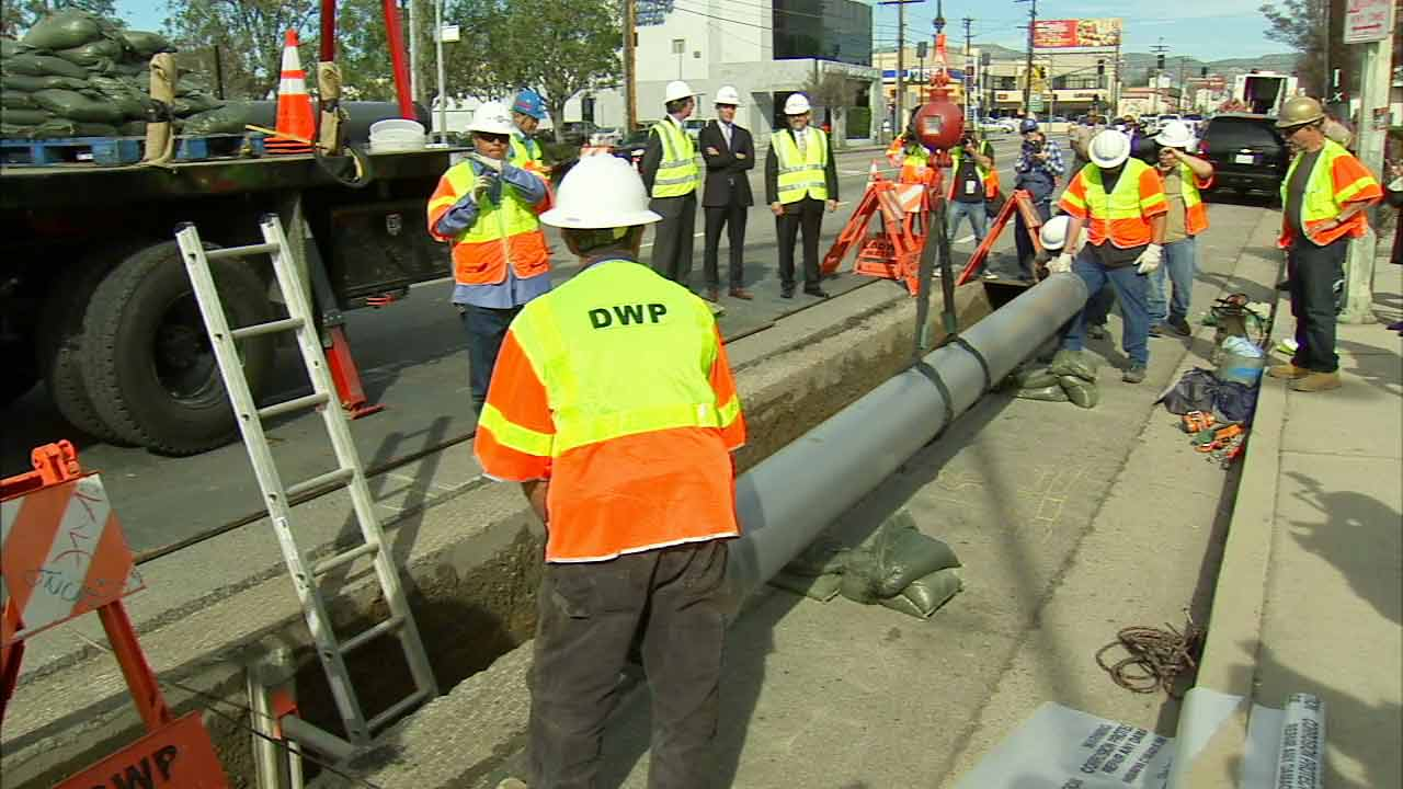 Department of Water and Power workers lower a water pipe into the ground in this 2015 photo.