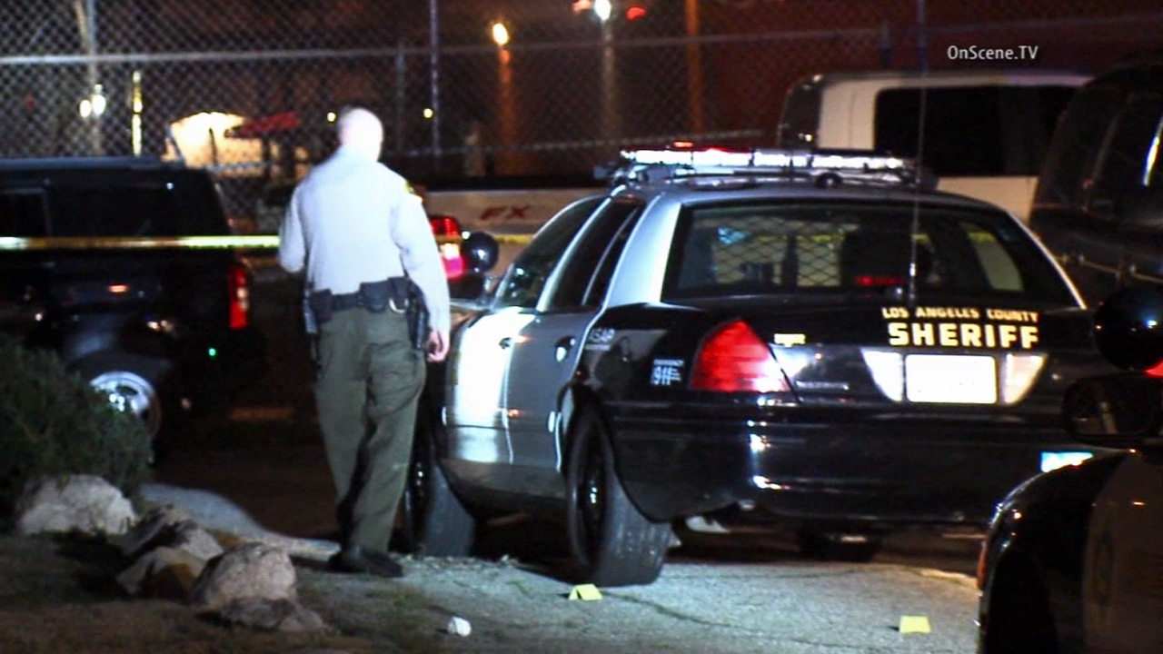 A Los Angeles County sheriff's deputy investigates the scene of a deputy-involved shooting in Lomita on Sunday, Jan. 18, 2015.