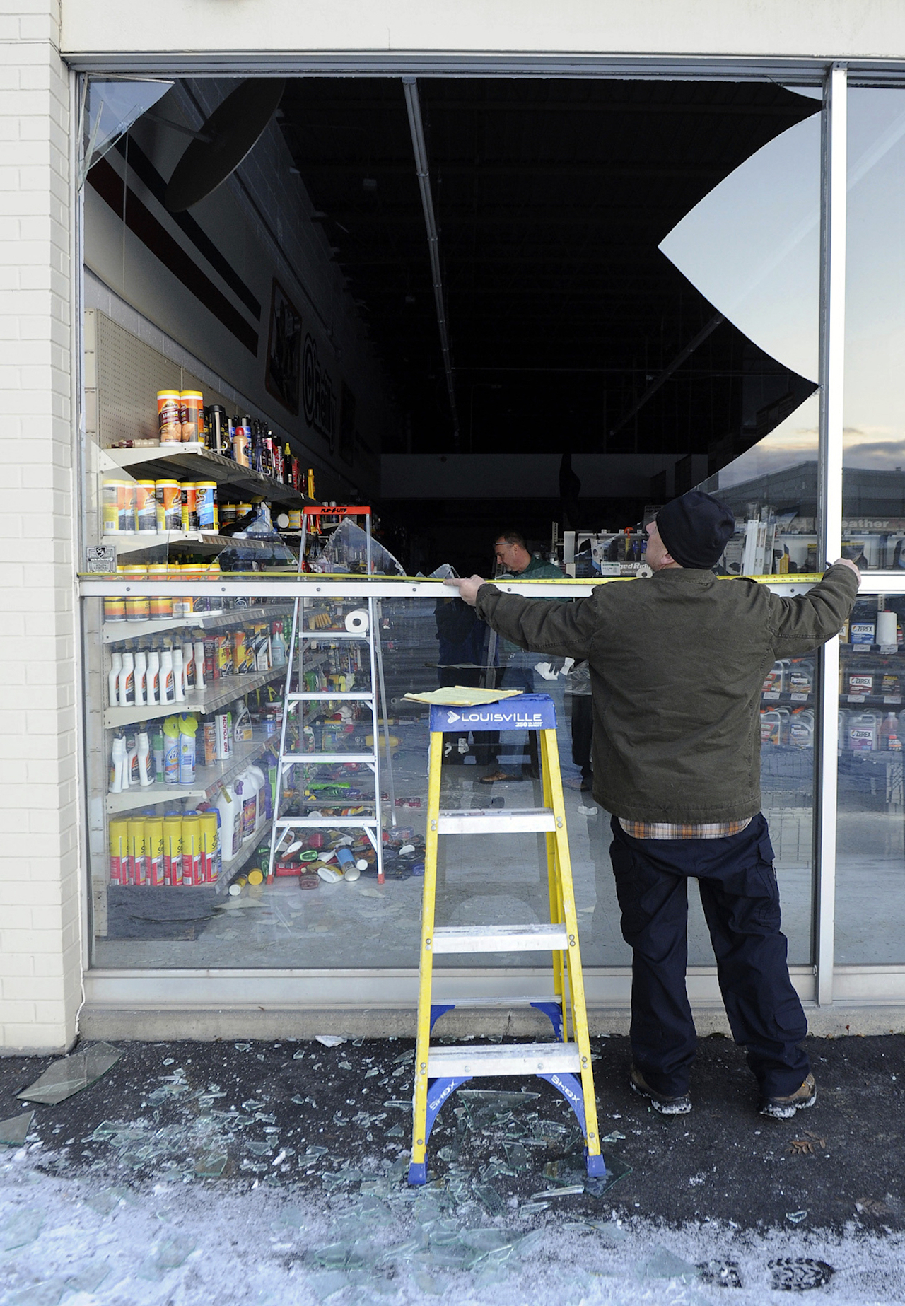 <div class='meta'><div class='origin-logo' data-origin='AP'></div><span class='caption-text' data-credit='AP Photo/Mike Dinneen'>Dennis Keeling of Instant Services measures to replace broken glass at an auto parts store in Anchorage following the morning's earthquake which caused damage to the local area.</span></div>