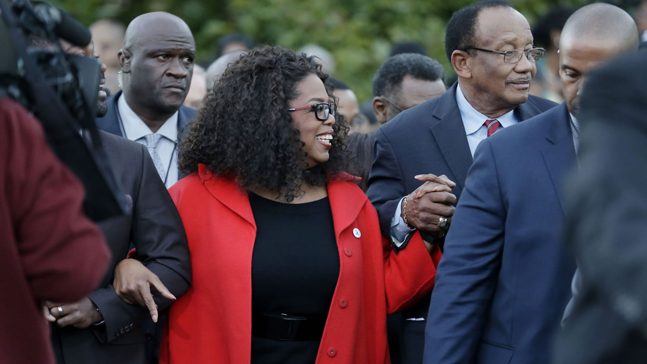 "Oprah locks arms with some of the cast of the movie ""Selma"" as they march to the Edmund Pettus Bridge in honor of Martin Luther King Jr., Jan. 18, 2015,  in Alabama (AP Photo)"