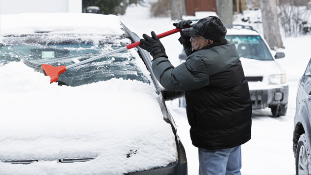 Clearing off a snow covered car