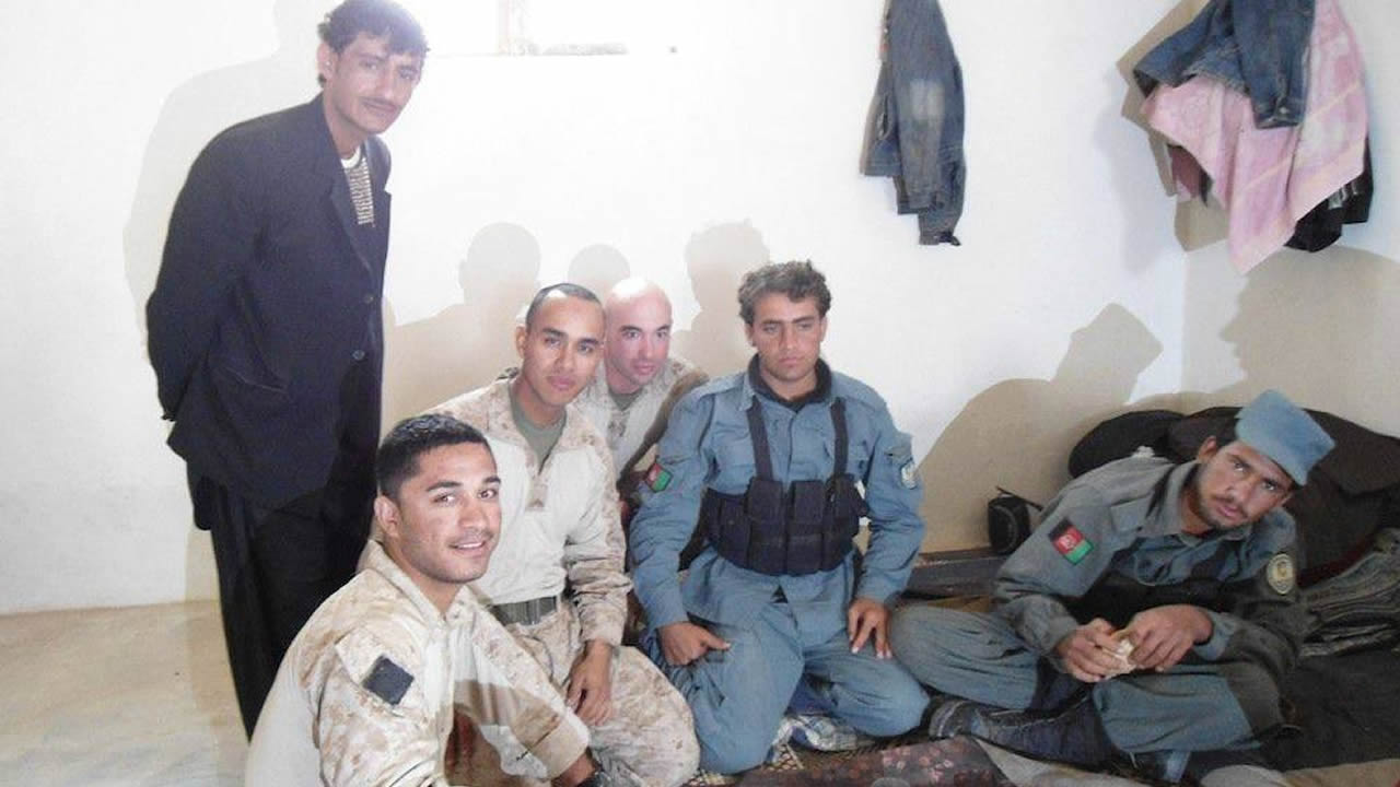 Mohammad Usafi, pictured front left, shares a meal in Afghanistan alongside his Marine brothers.