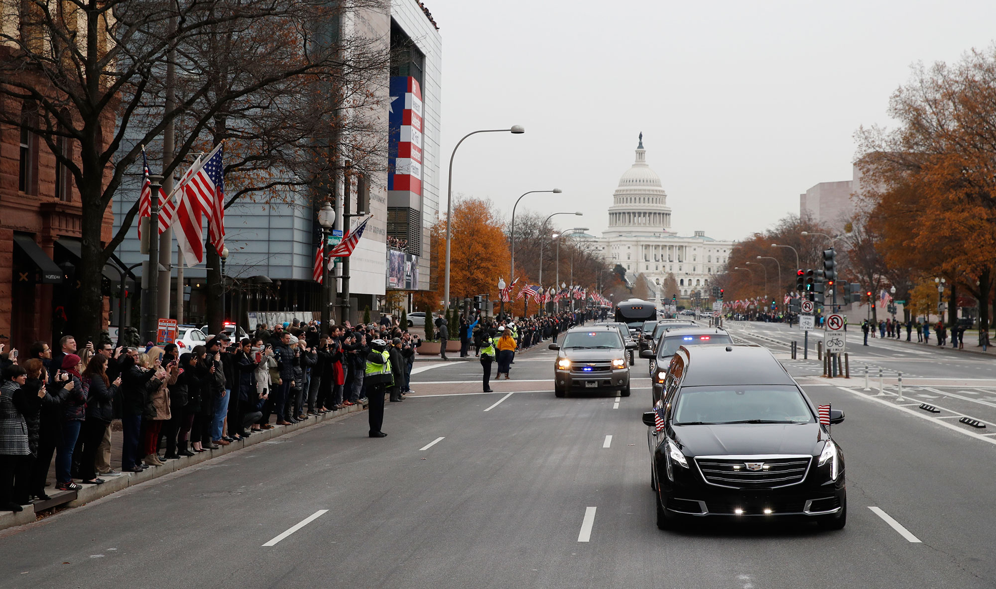"<div class=""meta image-caption""><div class=""origin-logo origin-image none""><span>none</span></div><span class=""caption-text"">People line Pennsylvania Ave. as the hearse passes by carrying the flag-draped casket of former President George H.W. Bush as it drives away from the Capitol. (Alex Brandon, Pool/AP Photo)</span></div>"