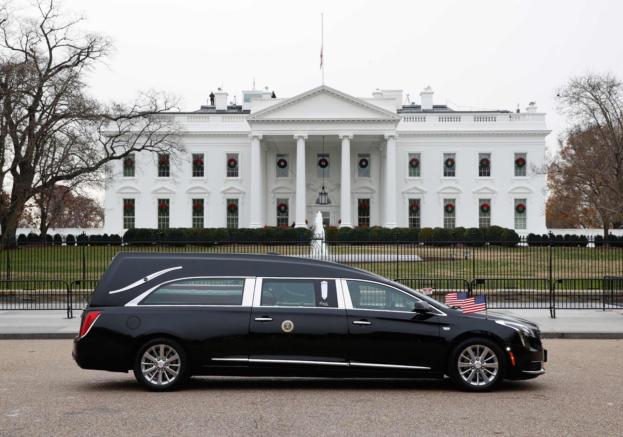 "<div class=""meta image-caption""><div class=""origin-logo origin-image none""><span>none</span></div><span class=""caption-text"">The hearse carrying the flag-draped casket of former President George H.W. Bush passes by the White House from the Capitol, heading to a State Funeral at the National Cathedral. (Jacquelyn Martin/AP Photo)</span></div>"