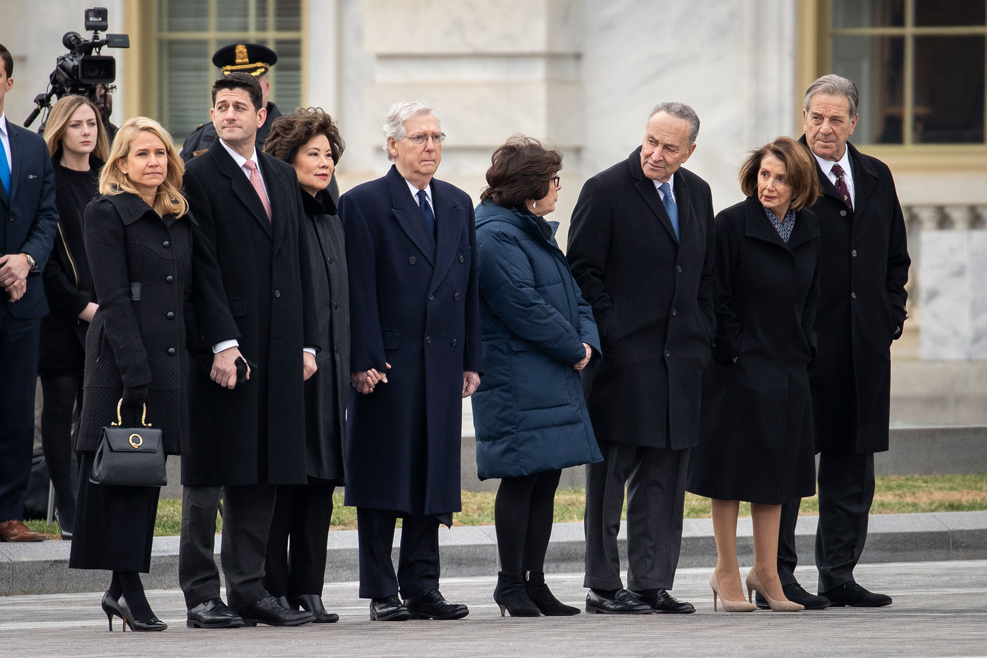 "<div class=""meta image-caption""><div class=""origin-logo origin-image none""><span>none</span></div><span class=""caption-text"">Janna Ryan, Paul Ryan, Elaine Chao, Mitch McConnell, Iris Weinshall, Chuck Schumer, Nancy Pelosi and Paul Pelosi await the departure of the casket.</span></div>"