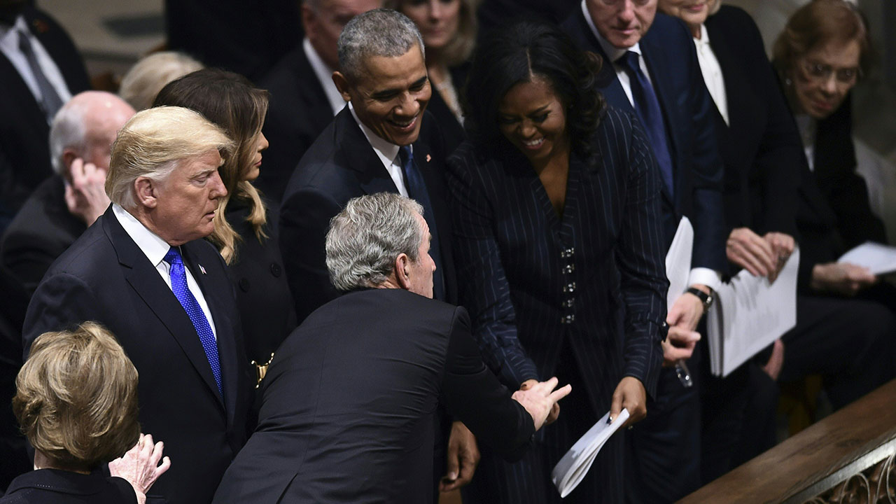 "<div class=""meta image-caption""><div class=""origin-logo origin-image none""><span>none</span></div><span class=""caption-text"">Former president George W. Bush greets former first Lady Michelle Obama at the funeral of his father George H.W. Bush. (BRENDAN SMIALOWSKI/AFP/Getty Images)</span></div>"