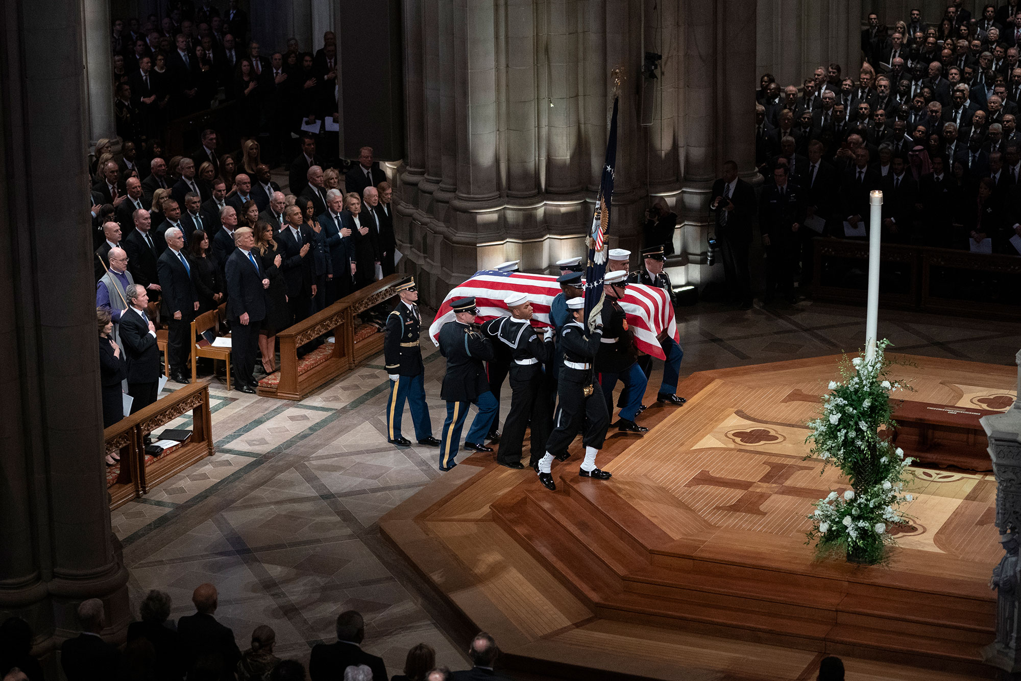 "<div class=""meta image-caption""><div class=""origin-logo origin-image none""><span>none</span></div><span class=""caption-text"">The flag-draped casket of former President George H.W. Bush is carried by a military honor guard. (Carolyn Kaster/AP Photo)</span></div>"