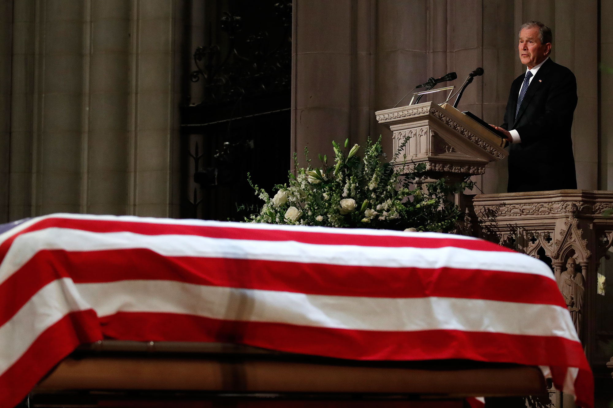 "<div class=""meta image-caption""><div class=""origin-logo origin-image none""><span>none</span></div><span class=""caption-text"">Former President George W. Bush speaks in front of the flag-draped casket of his father. (Alex Brandon, Pool/AP Photo)</span></div>"