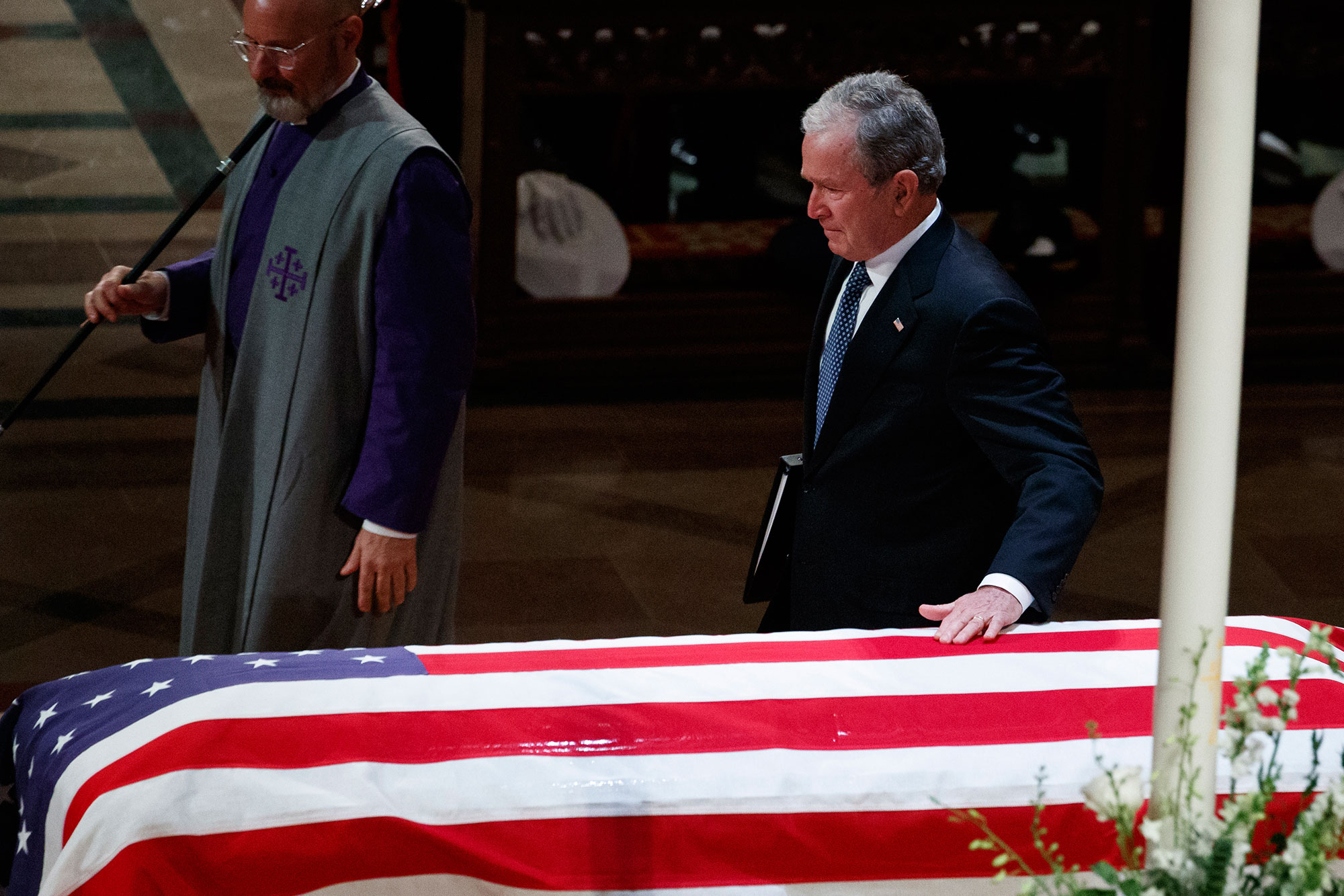 "<div class=""meta image-caption""><div class=""origin-logo origin-image none""><span>none</span></div><span class=""caption-text"">Former President George W. Bush touches his fathers casket after speaking during the State Funeral for former President George H.W. Bush, at the National Cathedral, Wednesday. (Evan Vucci/AP Photo)</span></div>"