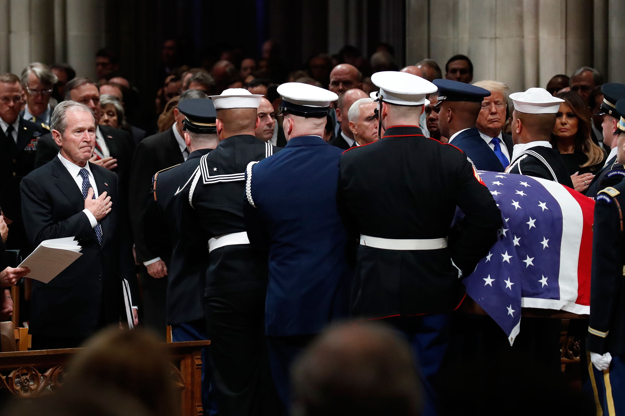 "<div class=""meta image-caption""><div class=""origin-logo origin-image none""><span>none</span></div><span class=""caption-text"">Former President George W. Bush places his hand over his heart as the flag-draped casket of former President George H.W. Bush is carried. (Alex Brandon, Pool/AP Photo)</span></div>"