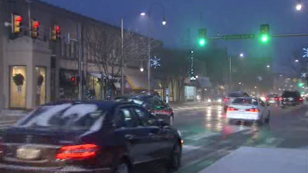 Cars at a traffic light in a snow storm.