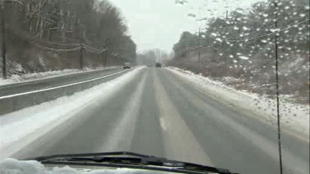 Car driving up a snowy hill.