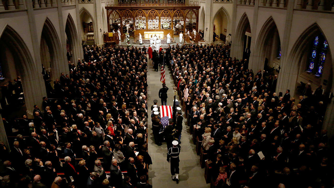 "<div class=""meta image-caption""><div class=""origin-logo origin-image none""><span>none</span></div><span class=""caption-text"">The flag-draped casket of former President George H.W. Bush is carried by a joint services military honor guard into St. Martin's Episcopal Church in Houston on Dec. 6, 2018. (Mark Humphrey/AP Photo)</span></div>"