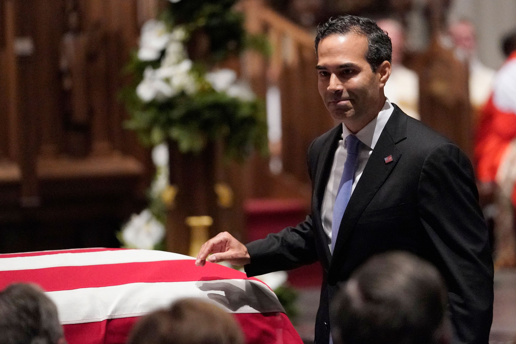 <div class='meta'><div class='origin-logo' data-origin='none'></div><span class='caption-text' data-credit='David J. Phillip, Pool/AP Photo'>George P. Bush walks past the casket of former President George H.W. Bush after giving a eulogy at St. Martin's Episcopal Church.</span></div>