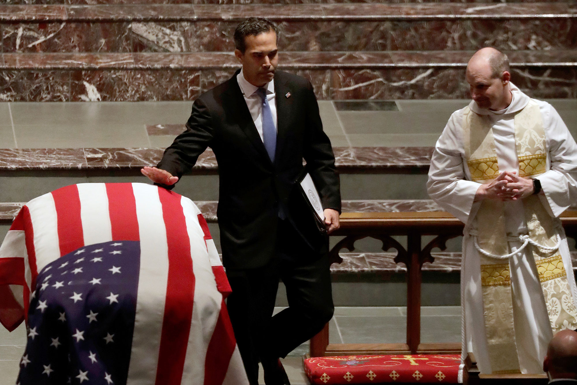 <div class='meta'><div class='origin-logo' data-origin='none'></div><span class='caption-text' data-credit='Mark Humphrey/AP Photo'>George P. Bush touches the flag-draped casket after giving a eulogy during a funeral for former President George H.W. Bush at St. Martin's Episcopal Church Thursday, Dec. 6, 2018.</span></div>