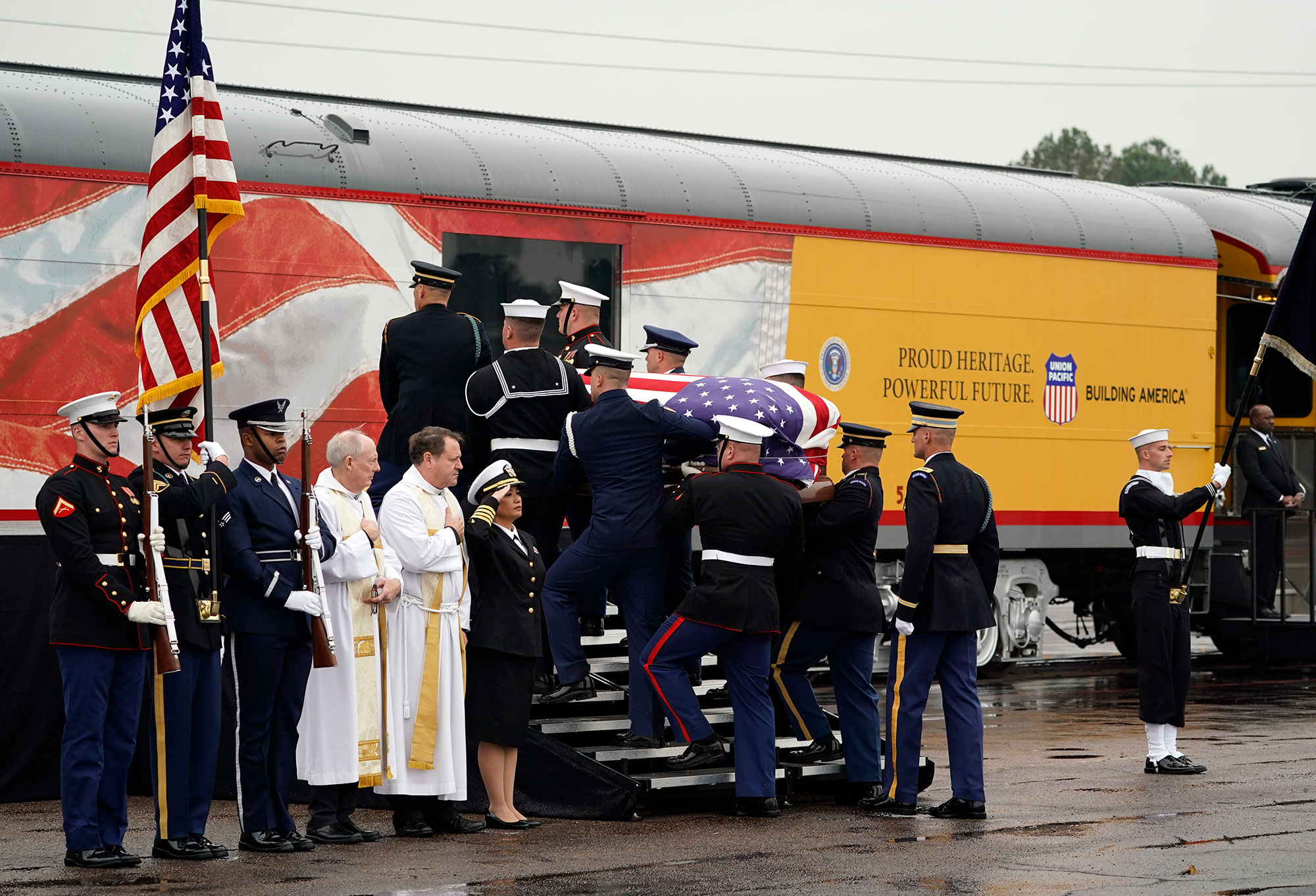 <div class='meta'><div class='origin-logo' data-origin='none'></div><span class='caption-text' data-credit='David J. Phillip, Pool/AP Photo'>The flag-draped casket of former President George H.W. Bush is carried by a joint services military honor guard Thursday, Dec. 6, 2018, in Spring, Texas.</span></div>