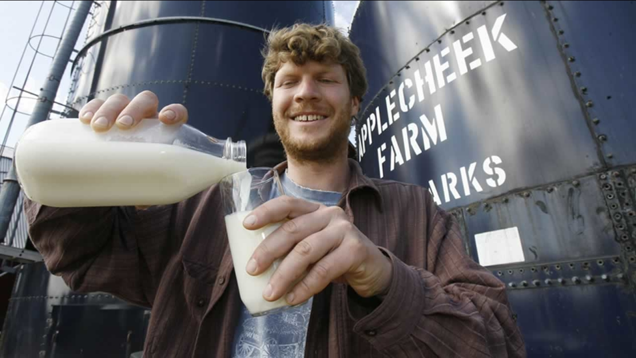 In this file photo, John Clark pours raw milk into a glass at Applecheek Farm in Hyde Park, Vt.,