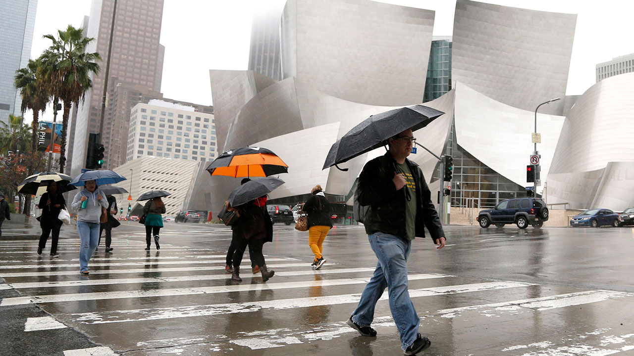 Pedestrians walk in the rain near downtown LA's Walt Disney Concert Hall on Thursday, Dec. 6, 2018.