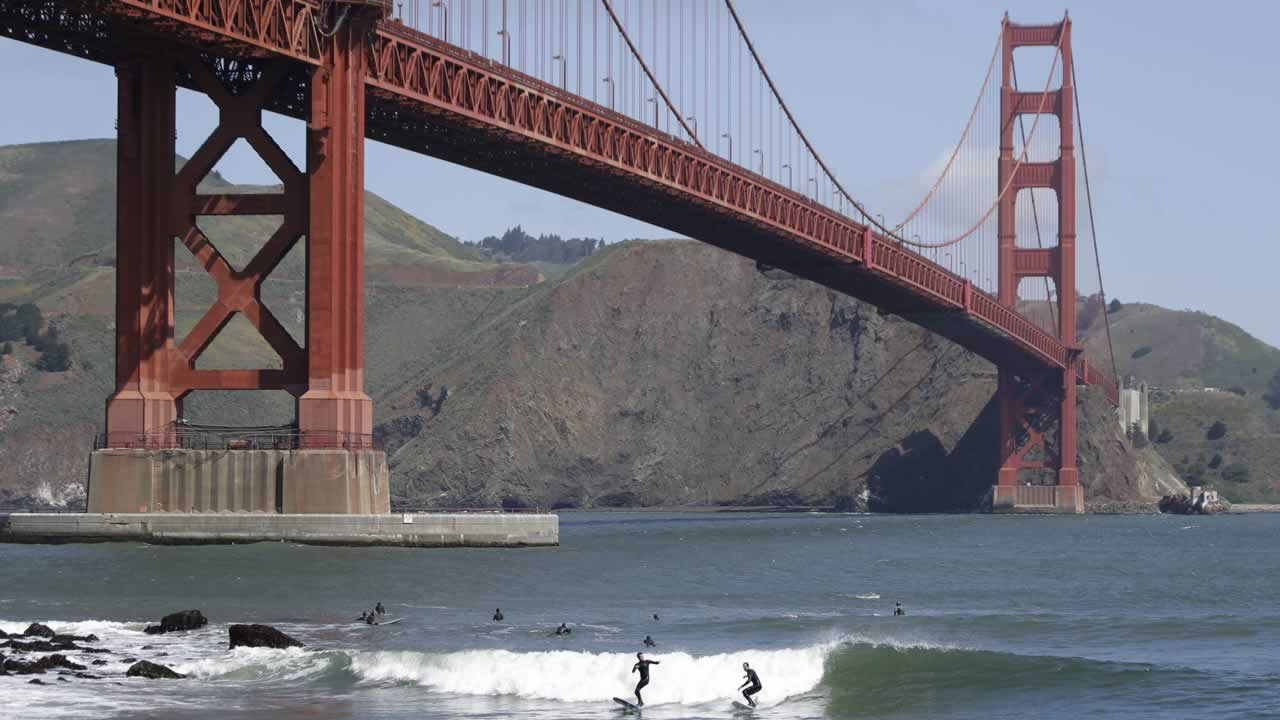 Two surfers ride a wave near Fort Point below the Golden Gate Bridge in San Francisco.
