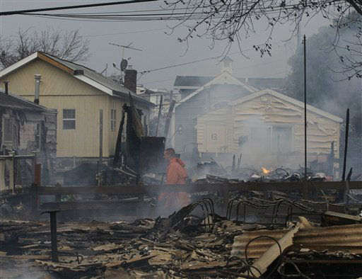 "<div class=""meta image-caption""><div class=""origin-logo origin-image none""><span>none</span></div><span class=""caption-text"">Keith Klein walks through homes damaged by a fire at Breezy Point in Queens, Oct. 30, 2012. The fire destroyed between 80 and 100 houses Monday night in an area flooded by Sandy. (AP Photo/ Frank Franklin II)</span></div>"