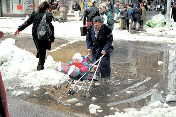 """<div class=""""meta image-caption""""><div class=""""origin-logo origin-image none""""><span>none</span></div><span class=""""caption-text"""">March 1993: A woman navigates a stroller through the aftermath of a blizzard in New York City. (Photo/Richard Drew)</span></div>"""