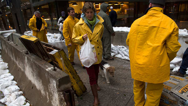 "<div class=""meta image-caption""><div class=""origin-logo origin-image none""><span>none</span></div><span class=""caption-text"">Woman walks her dog through a working crew as they stack sandbags beside concrete barriers to protect buildings from flooding near the World Financial Center in NYC, Oct. 29, 2012. (AP/John Minchillo)</span></div>"