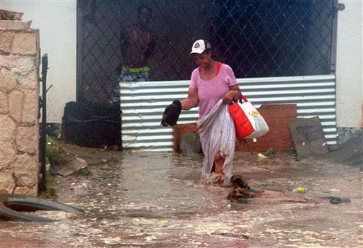 "<div class=""meta image-caption""><div class=""origin-logo origin-image none""><span>none</span></div><span class=""caption-text"">A woman wades through flood water brought by Hurricane Sandy as she evacuates her home in the Caribbean Terrace neighborhood of eastern Kingston, Jamaica, Wednesday, Oct. 24, 2012. (AP Photo/Collin Reid)</span></div>"
