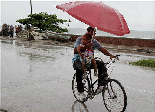 "<div class=""meta image-caption""><div class=""origin-logo origin-image none""><span>none</span></div><span class=""caption-text"">A man balances a child and umbrella on his bike as it rains during the approach of Hurricane Sandy in Manzanillo, Cuba, Wednesday, Oct. 24, 2012. (AP Photo/Franklin Reyes)</span></div>"