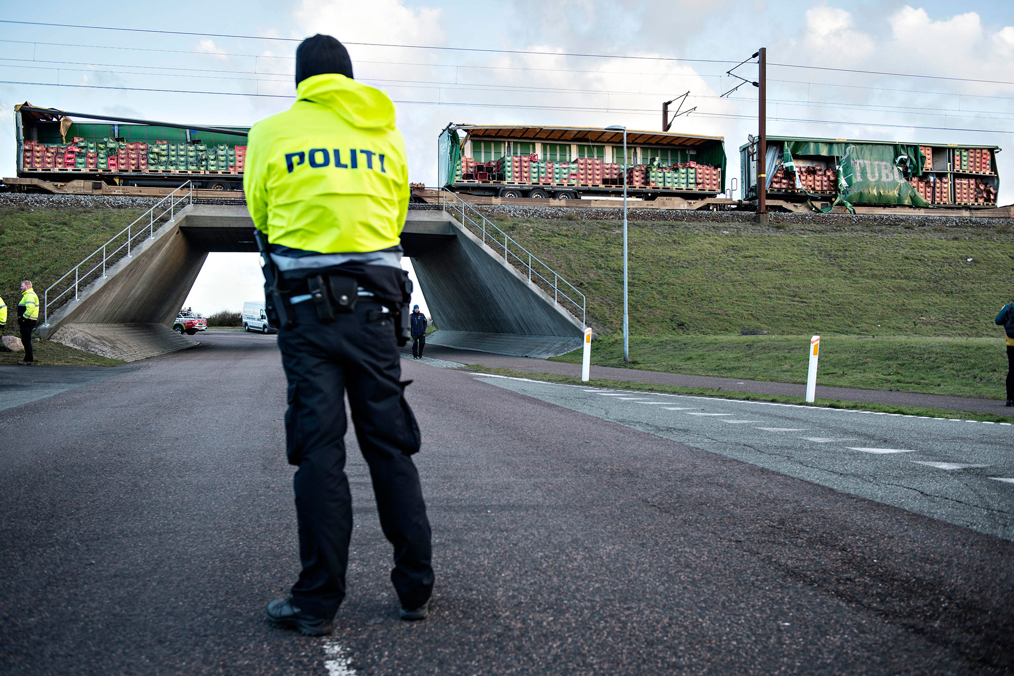 <div class='meta'><div class='origin-logo' data-origin='none'></div><span class='caption-text' data-credit='MICHAEL BAGER/AFP/Getty Images'>A policeman blocks the road as in background can be seen a cargo train with damaged containers after access to the Great Belt Bridge was closed following a railway accident.</span></div>