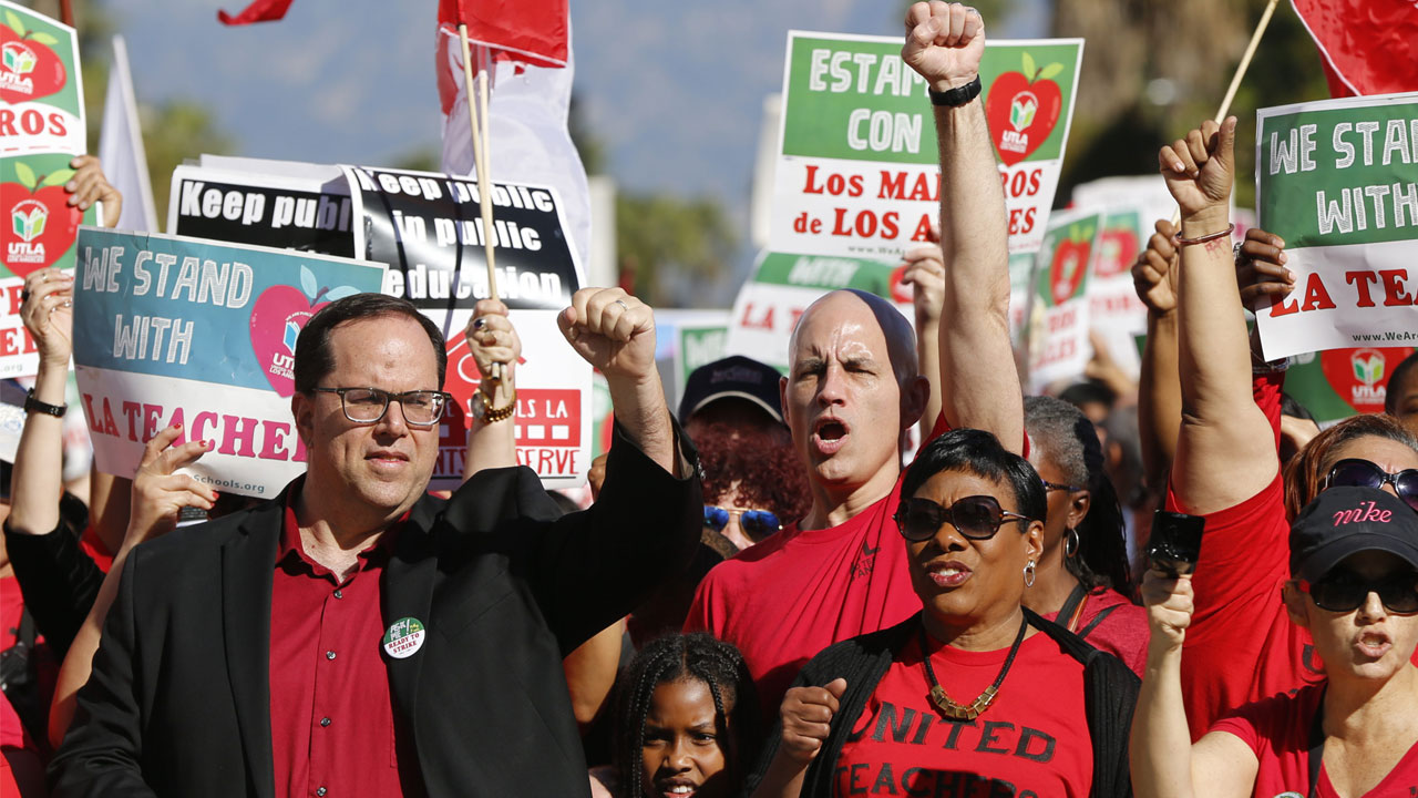 <div class='meta'><div class='origin-logo' data-origin='AP'></div><span class='caption-text' data-credit='AP Photo/Damian Dovarganes'>In this Dec. 15, 2018, photo, United Teachers Los Angeles, UTLA president, Alex Caputo-Pearl, left, joins teachers at a rally next in downtown Los Angeles.</span></div>