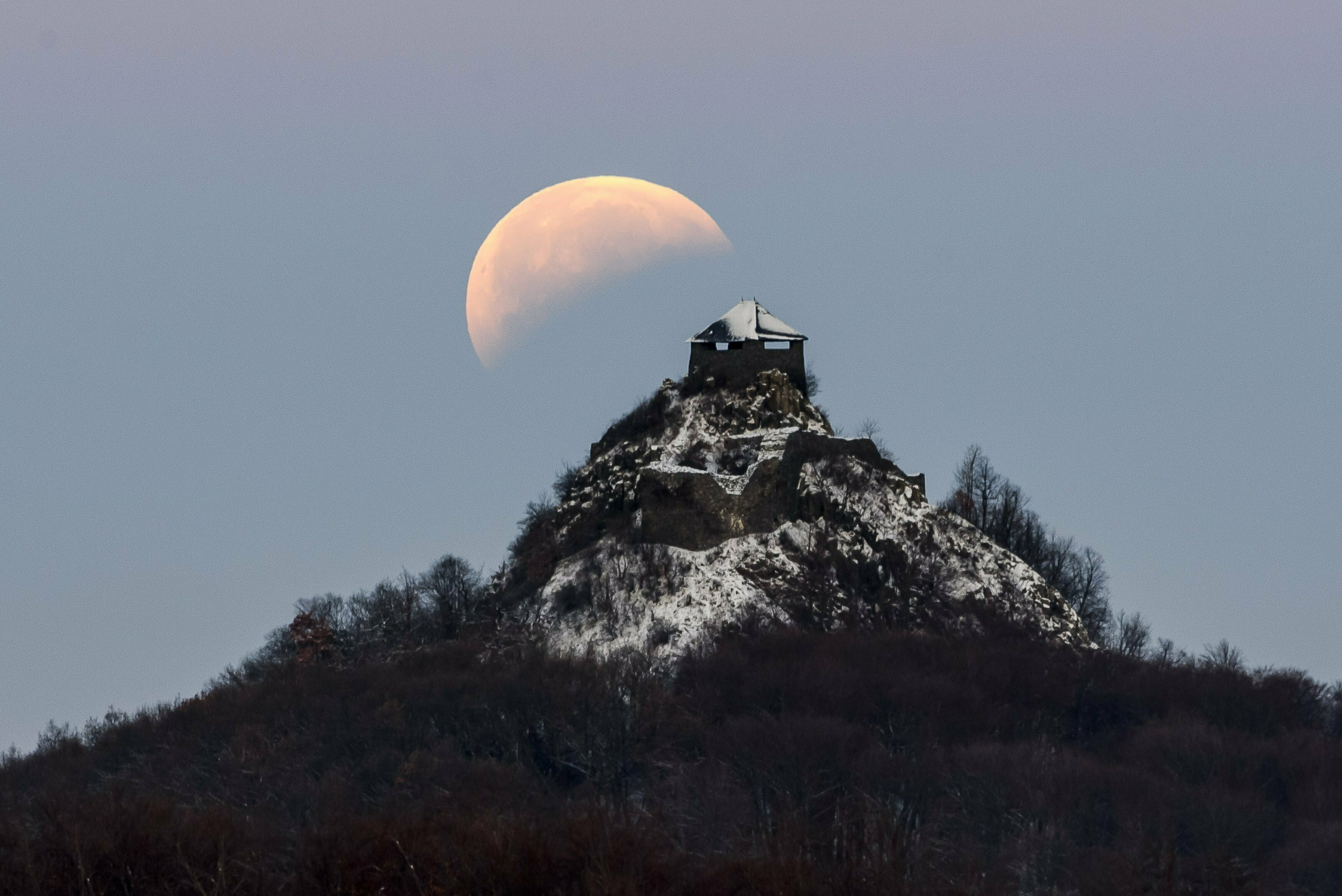 <div class='meta'><div class='origin-logo' data-origin='none'></div><span class='caption-text' data-credit='Peter Komka/MTI via AP'>The moon fully shadowed by the Earth is seen above the castle of Salgo during a total lunar eclipse near Salgotarjan, Hungary, early Monday, Jan. 21, 2019.</span></div>