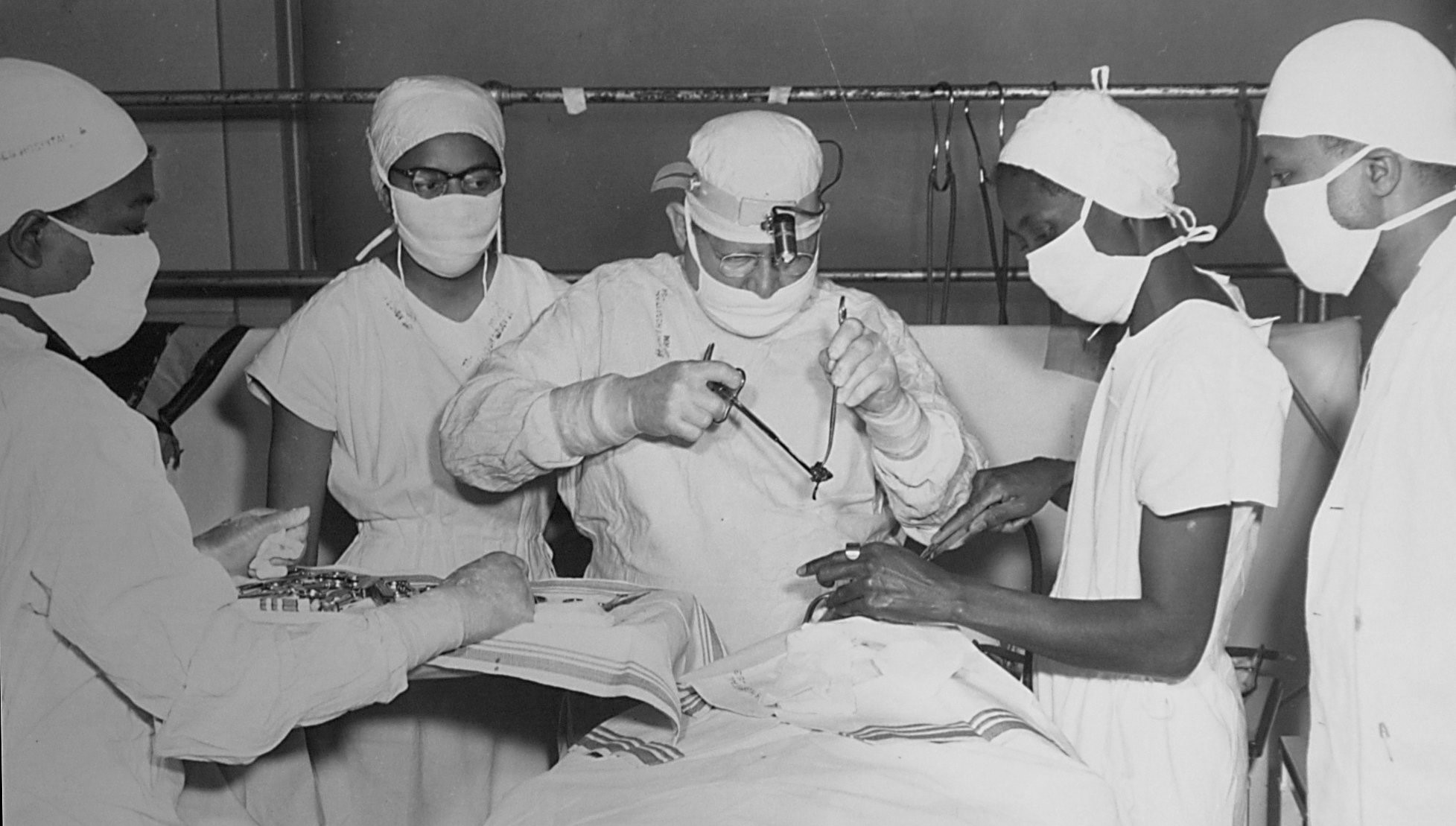 <div class='meta'><div class='origin-logo' data-origin='none'></div><span class='caption-text' data-credit='(Source: Saint Augustine's College Archive)'>Dr. Ballou (center) does a tonsillectomy at St. Agnes Hospital in the late 1940's. Nurse Laura Evans Kelley (to his right) assists.</span></div>