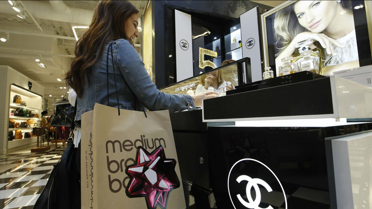 In this Nov. 28, 2014 file photo, a shopper buys Chanel perfume at a Bloomingdale's store at the Glendale Galleria shopping mall in Glendale, Calif.  (AP Photo/Damian Dovarganes, File)