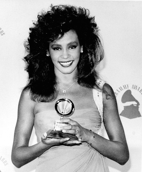 """<div class=""""meta image-caption""""><div class=""""origin-logo origin-image none""""><span>none</span></div><span class=""""caption-text"""">Feb. 1986: Houston poses with her Grammy backstage at the Grammy Awards after winning best female pop vocal performance for her song """"Saving All My Love For You."""" (Photo/AP Photo)</span></div>"""