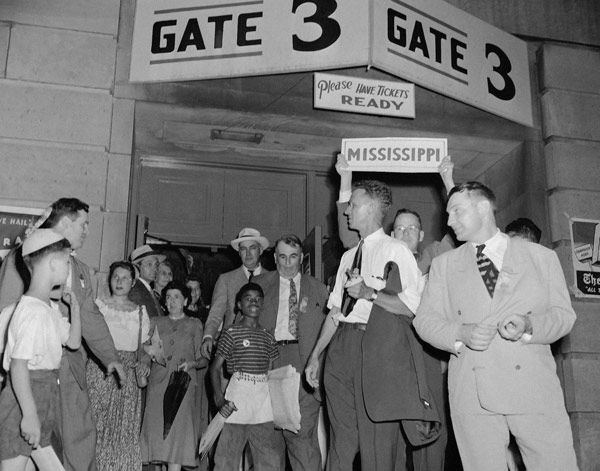 "<div class=""meta image-caption""><div class=""origin-logo origin-image none""><span>none</span></div><span class=""caption-text"">Members of the Mississippi walkout delegation gather under state banners outside Convention Hall after bolting Democratic National Convention in Philadelphia, July 14, 1948. (AP Photo)</span></div>"