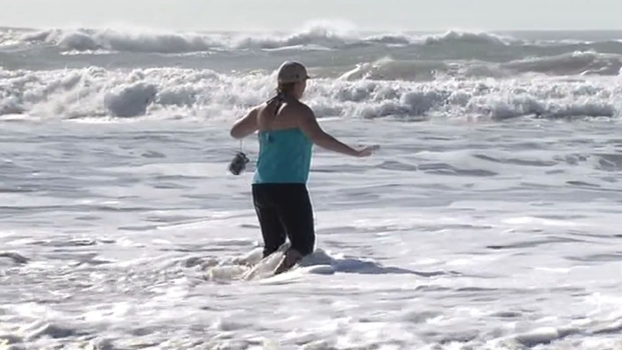 Woman wading in water at Ocean Beach in San Francisco during high surf warning.