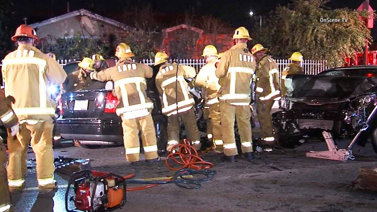 Firefighters are shown at the scene of a hit-and-run crash in South Los Angeles on Sunday, Feb. 15, 2015.