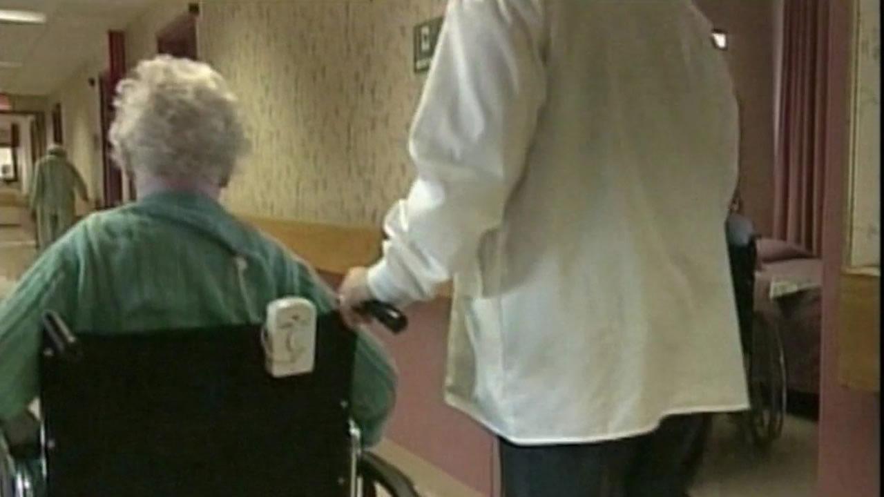 A medical professional walks an elderly woman in a wheelchair down a facility's hallway.