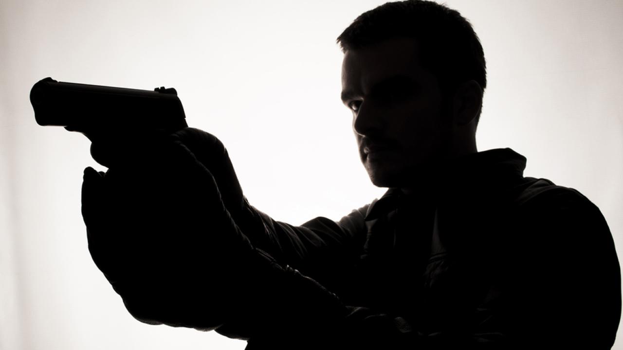 Silhouette of a man holding a gun.