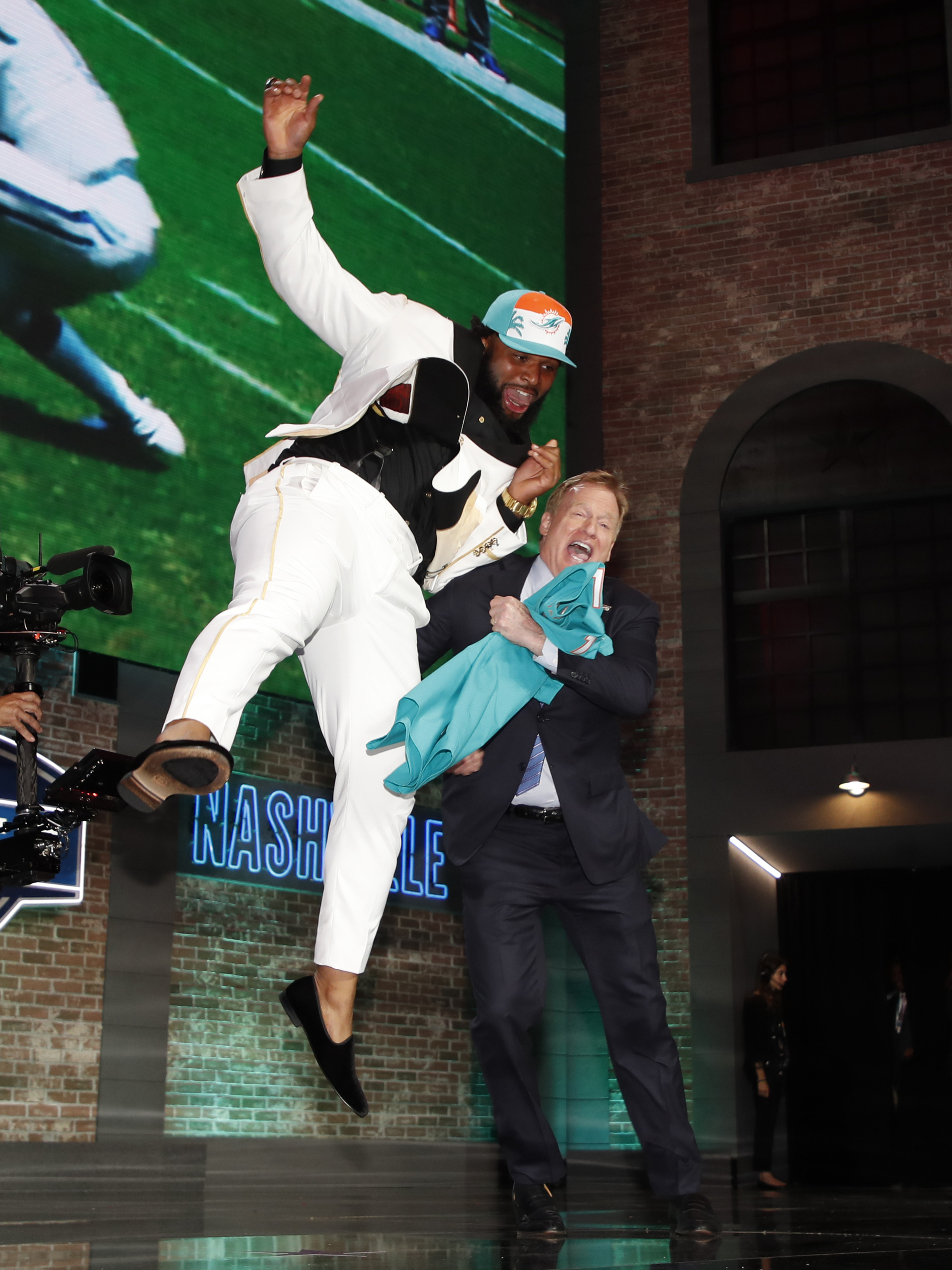 Christian Wilkins leaps into NFL Commissioner Roger Goodell after the Miami Dolphins selected Wilkins in the NFL football draft, Thursday, April 25, 2019, in Nashville, Tenn.