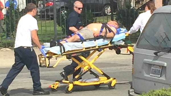 A man is being wheeled away in a gurney after being hit in an officer-involved shooting in Santa Ana. The man is suspected of stabbing a woman on Friday, Feb. 20, 2015.