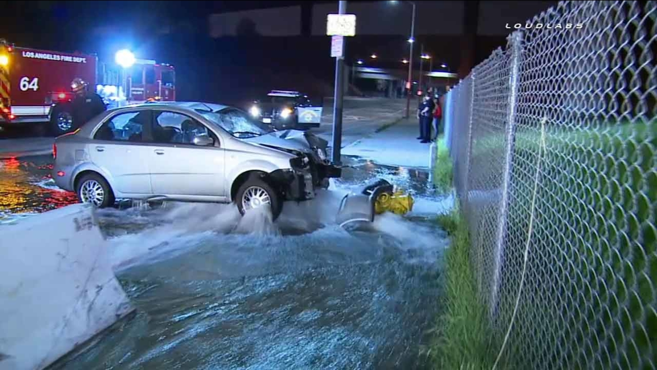Water is seen gushing onto South Los Angeles streets after a driver slammed a car into a fire hydrant on Sunday, Feb. 22, 2015.