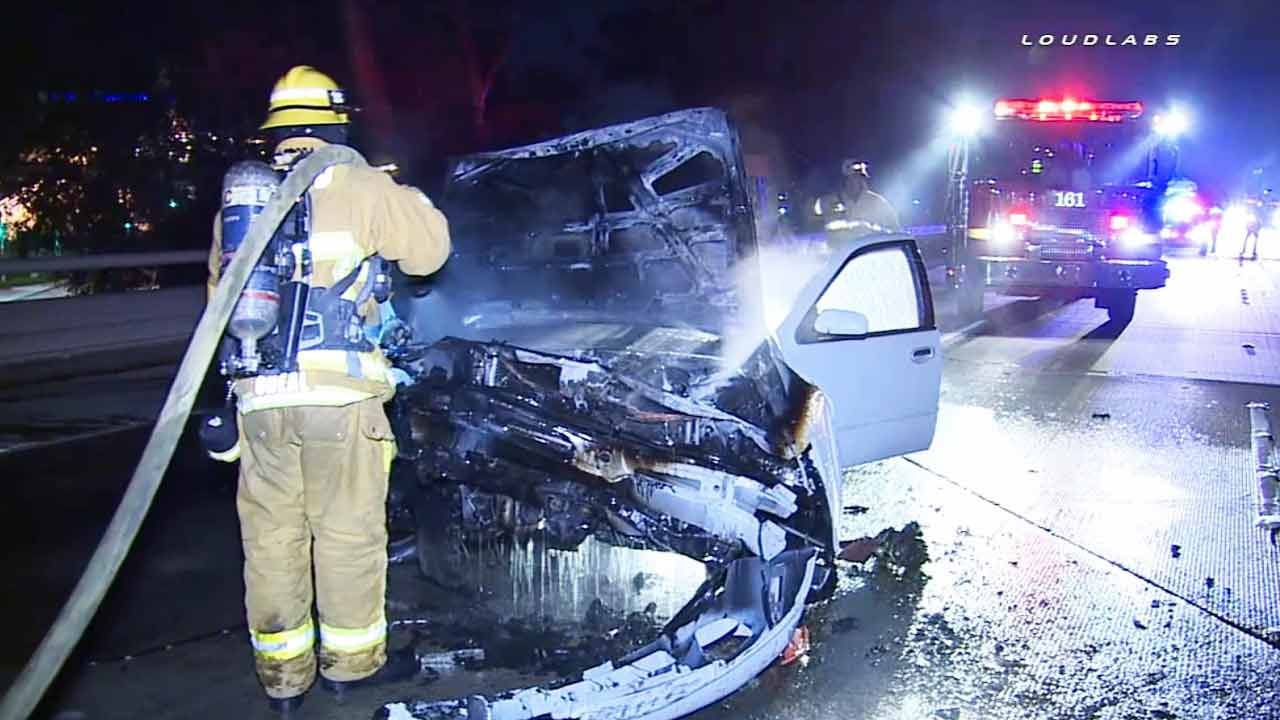 A firefighter douses a car destroyed by fire following a crash on the southbound 405 Freeway near Rosecrans Avenue in the Lawndale area on Sunday, Feb. 22, 2015.